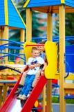 Группа в составе счастливые дети сползая в красочную спортивную площадку Стоковая Фотография RF