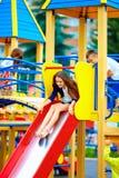 Группа в составе счастливые дети сползая в красочную спортивную площадку Стоковая Фотография