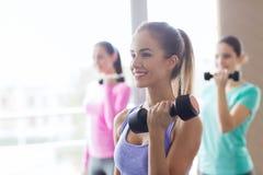 Группа в составе счастливые женщины с гантелями в спортзале Стоковые Фотографии RF