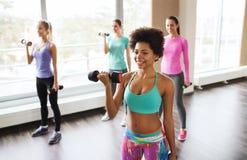 Группа в составе счастливые женщины с гантелями в спортзале Стоковая Фотография