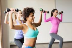 Группа в составе счастливые женщины с гантелями в спортзале Стоковое Изображение