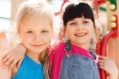 Группа в составе счастливые маленькие девочки на спортивной площадке детей стоковая фотография rf