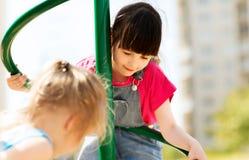 Группа в составе счастливые маленькие девочки на спортивной площадке детей стоковые изображения