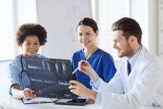 Группа в составе счастливые доктора обсуждая изображение рентгеновского снимка Стоковое Изображение