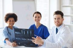 Группа в составе счастливые доктора обсуждая изображение рентгеновского снимка Стоковая Фотография RF