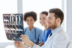 Группа в составе счастливые доктора обсуждая изображение рентгеновского снимка Стоковое Фото