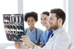 Группа в составе счастливые доктора обсуждая изображение рентгеновского снимка Стоковые Изображения RF