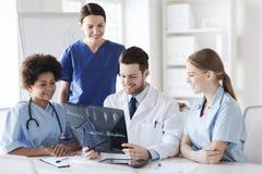 Группа в составе счастливые доктора обсуждая изображение рентгеновского снимка Стоковые Фото