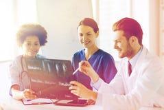 Группа в составе счастливые доктора обсуждая изображение рентгеновского снимка Стоковые Изображения