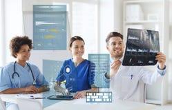 Группа в составе счастливые доктора смотря изображение рентгеновского снимка Стоковые Фото