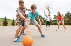 Группа в составе счастливые подростки играя баскетбол стоковое фото rf