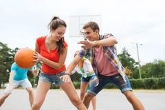 Группа в составе счастливые подростки играя баскетбол Стоковая Фотография RF