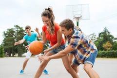 Группа в составе счастливые подростки играя баскетбол Стоковое Фото