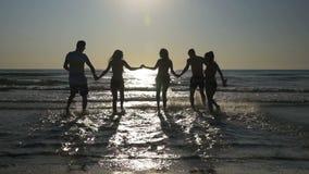 Группа в составе счастливые друзья бежать в море и играя в воде на восходе солнца в замедленном движении сток-видео