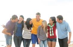 Группа в составе счастливые друзья говоря на пляже Стоковое Изображение