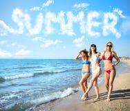 Группа в составе счастливые друзья имея потеху на пляже океана при слово лета сделанное из облаков Стоковая Фотография