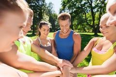 Группа в составе счастливые друзья с руками на верхней части outdoors Стоковые Фото