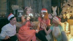 Группа в составе счастливые смеясь над друзья поднимая руки приближает к рождественской елке Партия торжества рождества акции видеоматериалы