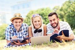 Группа в составе счастливые студенты изучая в парке Стоковая Фотография