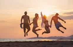 Группа в составе счастливые люди танцуя и скача внутри моря Стоковые Фото