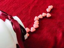 Группа в составе таблетки сердец с белой бутылкой на красной предпосылке ткани красный цвет поднял Стоковое Изображение RF