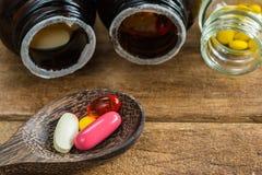 Группа в составе таблетки витамина дополнительные в деревянной ложке на деревянной таблице Стоковые Фото