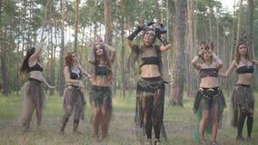 Группа в составе танцоры женщин с макияжем и в мистических фантастических костюмах танцуя шпунтовой танец в феях леса леса сток-видео