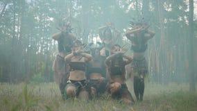 Группа в составе танцоры женщин с макияжем и в мистических фантастических костюмах танцуя шпунтовой танец в дыме цвета Лес акции видеоматериалы