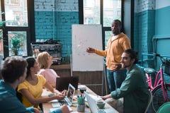 Группа в составе товарищи имея работу в офисе Стоковое Изображение
