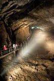 Группа в составе туристы идя на мост в Hall Muhajirs, самой большой зале пещеры нового Athos, абхазии стоковая фотография rf