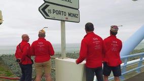 Группа в составе туристы в красной форме стоящая близко отметка Порту Moniz, смотрящ океан и имеющ потеху сток-видео