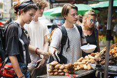 Группа в составе туристы покупая тайскую еду на стойле еды Стоковая Фотография