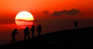 Группа в составе туристы принимает к горам на заходе солнца. Силуэт стоковые изображения rf