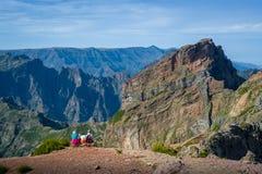 Группа в составе туристы сидит на скале и смотрит ландшафт горы Стоковое Изображение RF