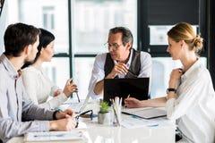 Группа в составе уверенно работники созывая собрание в офисе Стоковое Фото