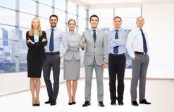 Группа в составе усмехаясь бизнесмены делая рукопожатие Стоковые Изображения RF