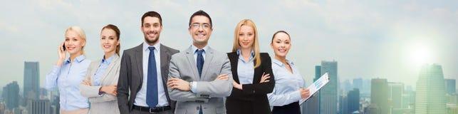 Группа в составе усмехаясь бизнесмены над предпосылкой города Стоковое Фото