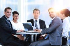 Группа в составе усмехаясь бизнесмены сидя в конференц-зале Стоковое Изображение