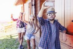 Группа в составе усмехаясь друзья в отдельном файле принимая смешное selfie Стоковое фото RF
