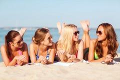 Группа в составе усмехаясь женщины в солнечных очках на пляже Стоковые Изображения