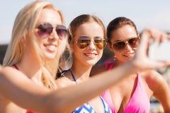 Группа в составе усмехаясь женщины делая selfie на пляже Стоковые Фото