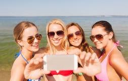 Группа в составе усмехаясь женщины делая selfie на пляже Стоковая Фотография