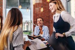 Группа в составе усмехаясь женщины обсуждая в офисе Стоковые Изображения