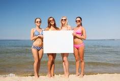Группа в составе усмехаясь женщины с пустой доской на пляже Стоковое Изображение