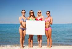 Группа в составе усмехаясь женщины с пустой доской на пляже Стоковые Изображения