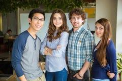 Группа в составе усмехаясь красивые содержимые уверенно студенты стоя совместно стоковые фотографии rf