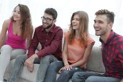 Группа в составе усмехаясь молодые люди сидя на кресле Стоковое фото RF