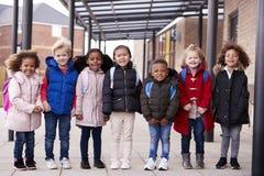 Группа в составе усмехаясь молодые мульти-этнические дети школы нося пальто и нося schoolbags стоя в ряд в дорожке вне их стоковые изображения rf