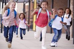 Группа в составе усмехаясь мульти-этнические дети школы бежать в дорожке вне их младенческого школьного здания после урока, конца стоковая фотография