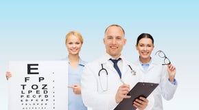 Группа в составе усмехаясь доктора с диаграммой глаза Стоковая Фотография